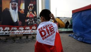 10 March 2011. Manama, Bahrain. Protest graffiti contrasts with modern developments; glittering malls contrast with the determined street protests camping out at Pearl Square, honking horns, waving flags and generally congregating to show their demands for freedom and equality. The killing of the protesters in the early days of the protests radicalised many who hadbeen against the demonstratiions. The number of predominantly black cloaked women and children is startling as the have decded to respond to the killings by coming out in droves.